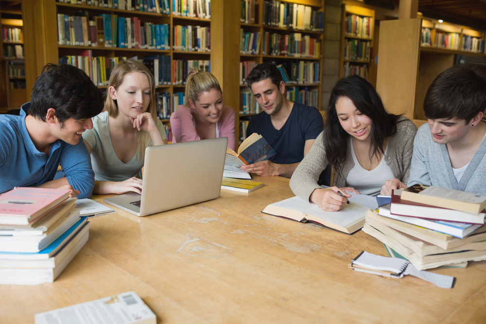 Students sitting at a table in a library while learning and working on a laptop-1