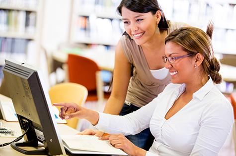 Librarian helping woman at computer