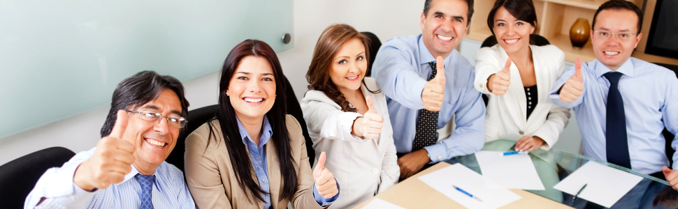 Businesspeople all sitting at a table giving a thumbs up